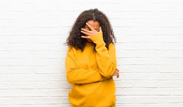 Parecendo estressado, envergonhado ou chateado, com dor de cabeça, cobrindo o rosto com a mão
