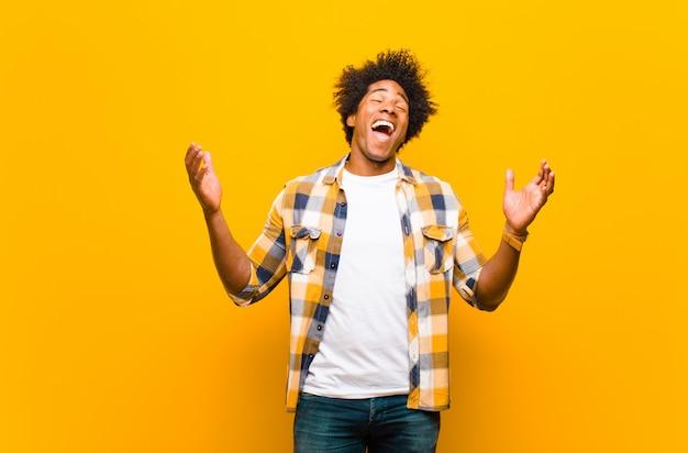 Parecendo extremamente feliz e surpreso, comemorando o sucesso, gritando e pulando