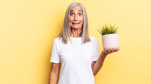 Parecendo feliz e agradavelmente surpreso, animado com uma expressão fascinada e chocada segurando uma planta decorativa