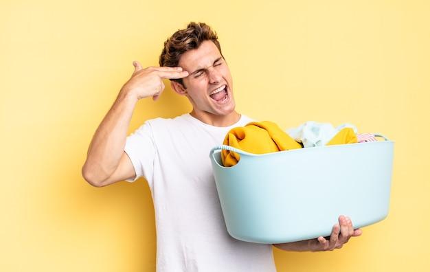 Parecendo infeliz e estressado, gesto de suicídio fazendo sinal de arma com a mão, apontando para a cabeça. conceito de lavagem de roupas