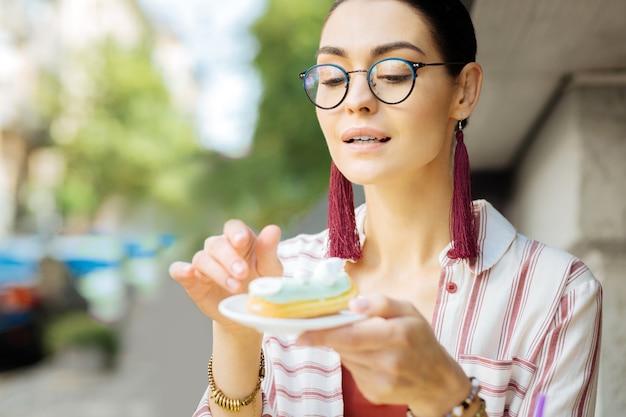 Parecendo interessado. calma jovem de óculos e interessado enquanto olha a éclair no prato