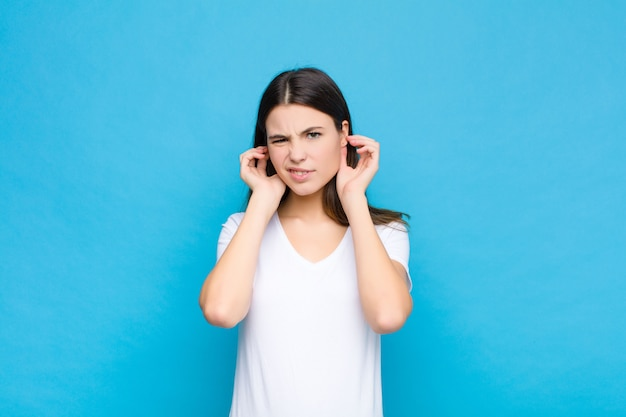 Parecendo irritado, estressado e irritado, cobrindo os dois ouvidos com um barulho ensurdecedor, som ou música alta