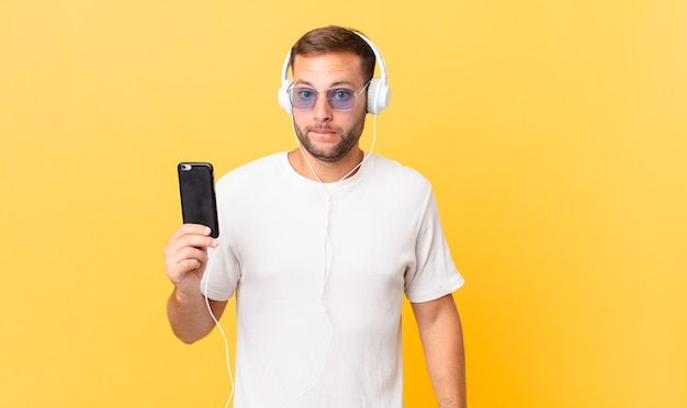 Parecendo perplexo e confuso, ouvindo música com fones de ouvido e um smartphone