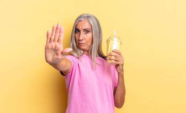 Parecendo sério, severo, descontente e irritado mostrando a palma da mão aberta fazendo um gesto de pare e segurando um milkshake