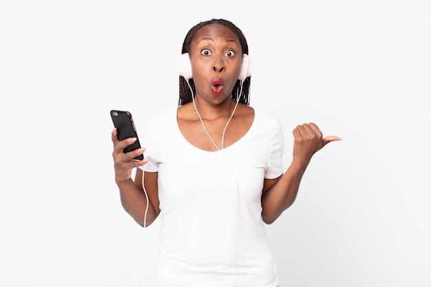 Parecendo surpreso e descrente com fones de ouvido e um smartphone
