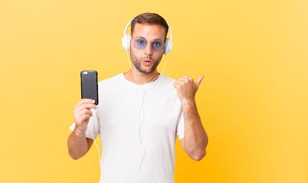 Parecendo surpreso e descrente, ouvindo música com fones de ouvido e um smartphone