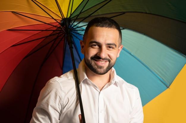 Parecendo um cara bonito e feliz com uma camisa branca e um guarda-chuva colorido arco-íris atrás