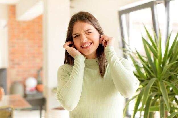Parecendo zangado, estressado e irritado, cobrindo ambos os ouvidos para um barulho, som ou música alta ensurdecedores