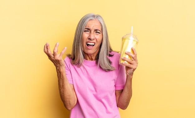 Parecendo zangado, irritado e frustrado, gritando wtf ou o que há de errado com você e segurando um milkshake