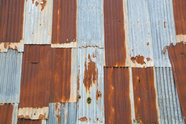 Parede abandonada de ferro enferrujado galvanizado com zinco como fundo de textura vintage
