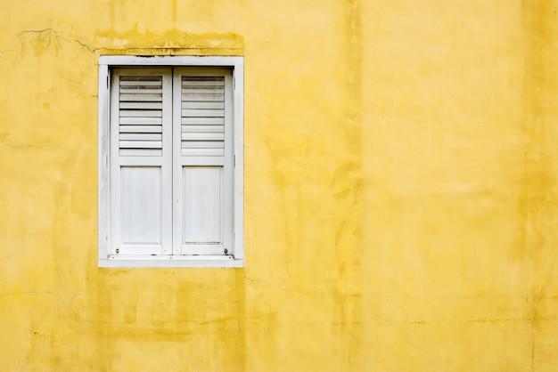 Parede amarela e uma janela branca