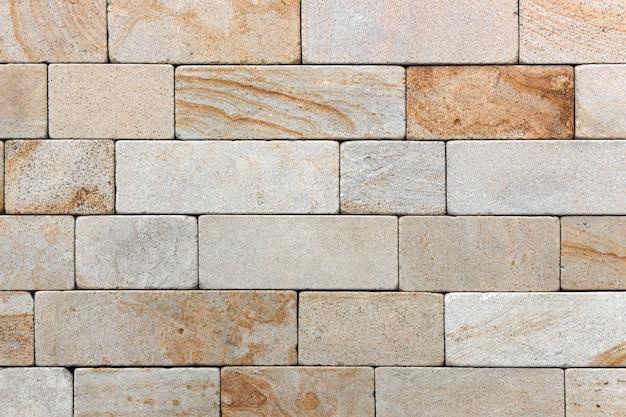 Parede amarela feita de pedra natural, azulejo decorativo ecológico. plano de fundo ou textura.
