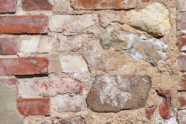 Parede antiga feita de pedras de granito e tijolos