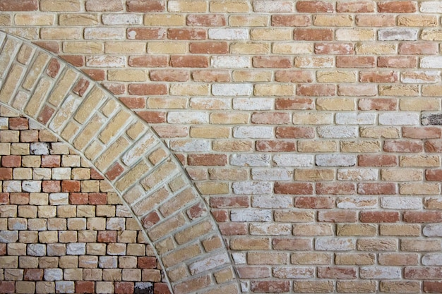Parede antiga feita de tijolos marrons laranja com parte inserida de um círculo curvo