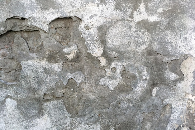Parede antiga resistida com prédio antigo de fundo cinza. gesso cinza descascado rachado.