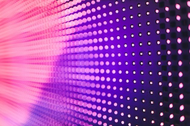 Parede azul colorida brilhante do diodo emissor de luz com teste padrão cor-de-rosa - fundo ascendente próximo.