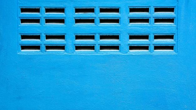 Parede azul com grelhas de ventilação