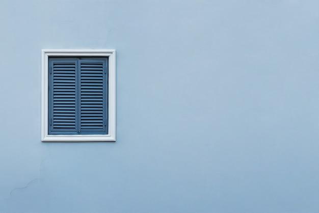 Parede azul da casa com uma janela fechada à esquerda e detalhes.