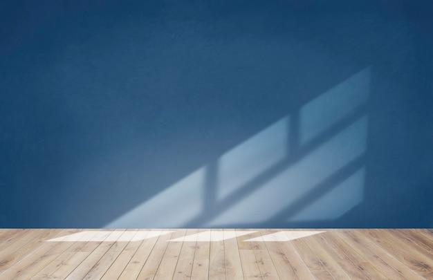 Parede azul em uma sala vazia com piso de madeira