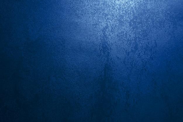 Parede azul escura com estuque decorativo. fumaça, fumaça, holofotes