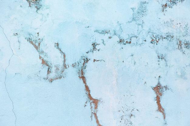 Parede azul pastel velha com escoriações