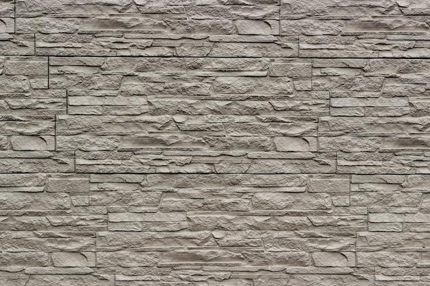Parede bege decorativa da pedra rasgada artificial como um fundo ou uma textura.