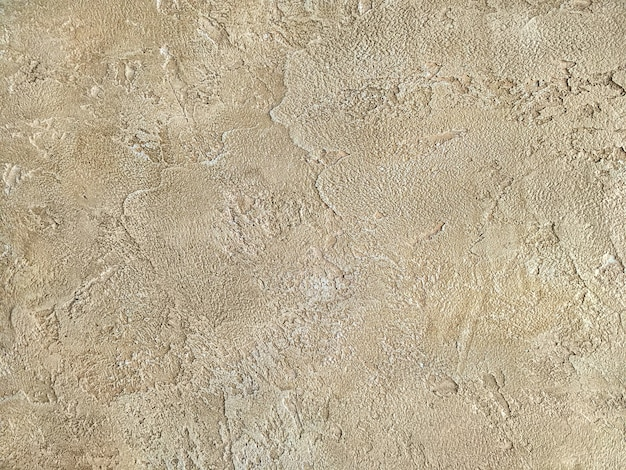 Parede bege velha coberta com o emplastro desigual. textura da superfície gasto da pedra da areia do vintage, close up.