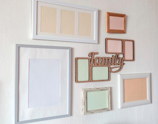 Parede branca com conjunto de diferentes molduras vazias verticais e horizontais para criar galeria de fotos de família na parede, para capturar um momento, modelo de maquete na parede branca, estilo de vida