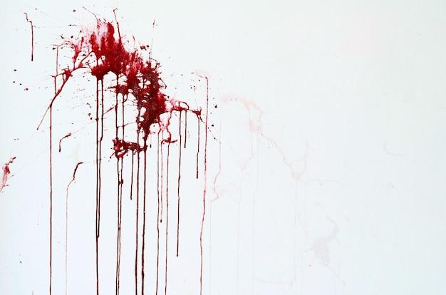 Parede branca de cimento de textura de fundo com manchas de tinta vermelhas como sangue