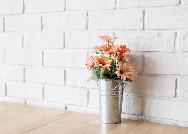 Parede branca e mesa de madeira flor decorativa