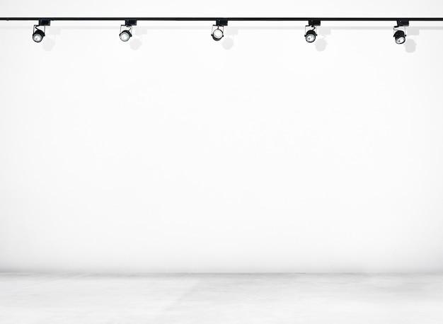 Parede branca e piso de concreto com holofotes