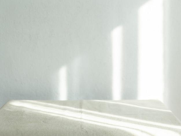 Parede branca vazia com a luz do sol brilhando através de uma janela - conceito de raios solares para sobrepor uma foto.