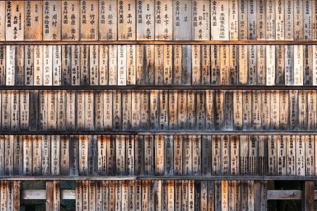 Parede cheia de tábuas de madeira envelhecidas (ema) com os nomes dos doadores e datas na entrada do santuário fushimi inari em kyoto, japão.