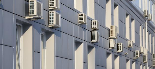 Parede cinza de edifício de escritórios feitos de placas de metal com janelas e condicionadores de ar