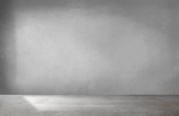 Parede cinza em um quarto vazio com piso de concreto