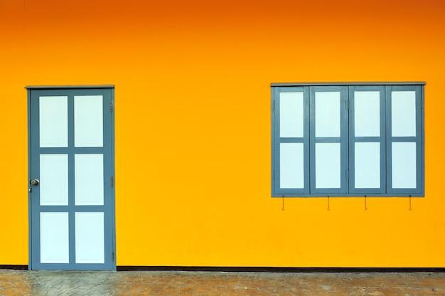Parede colorida com uma porta e um bloco de janelas