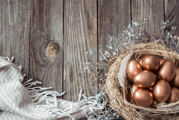 Parede com ovos de páscoa dourados na parede de madeira.