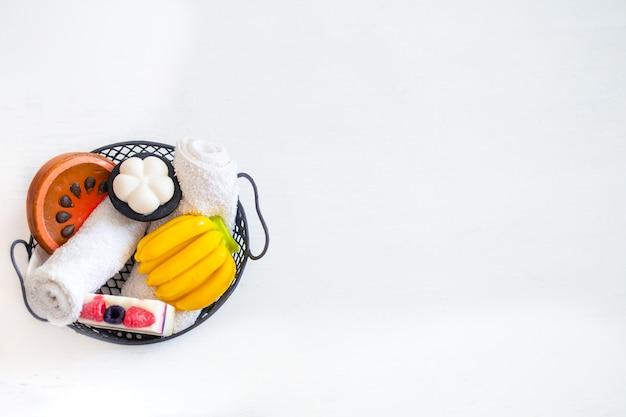 Parede com sabonete artesanal em forma de fruta em uma cesta em uma parede de madeira clara. conceito de beleza e cuidados com o corpo.