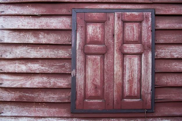 Parede com textura de madeira, janela com venezianas vermelhas antigas, piso de madeira estilo tailandês