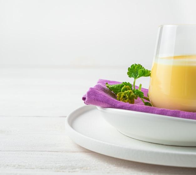 Parede com uma parte de um copo com uma bebida de manga com leite em uma parede de luz. vista lateral, copie o espaço.