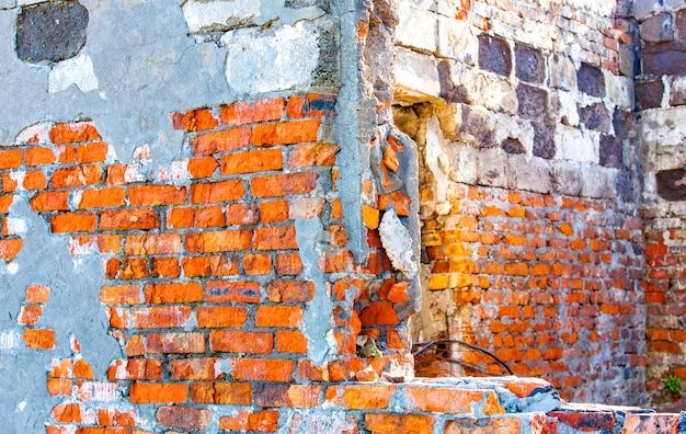 Parede da casa, parede de tijolo vermelho com um furo para a janela.