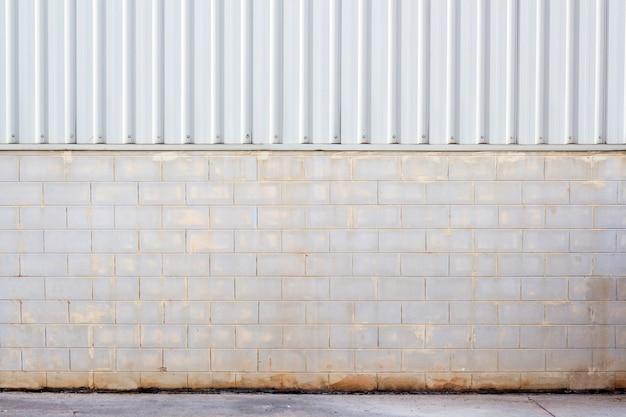 Parede da fábrica feita de folha de metal e bloco de pedra, planta de parede de cor creem