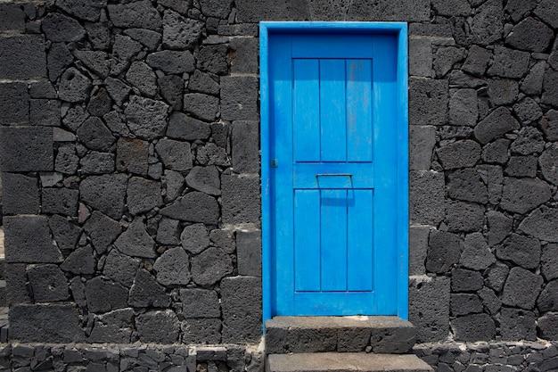 Parede de alvenaria de pedra de lava porta azul em la palma