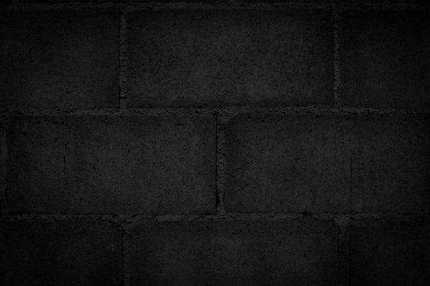 Parede de bloco preto escuro que não é rebocada