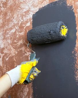 Parede de casa pintada à mão com tinta acrílica cinza com um rolo em luvas de trabalho amarelas.