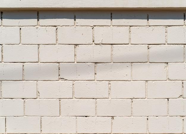 Parede de cimento branco-creme com padrão de tijolo no campo ao ar livre para segundo plano.