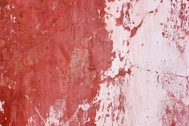 Parede de cimento com tinta vermelha, fundo áspero. fundo concreto abstrato com pintura vermelha da casca velha.