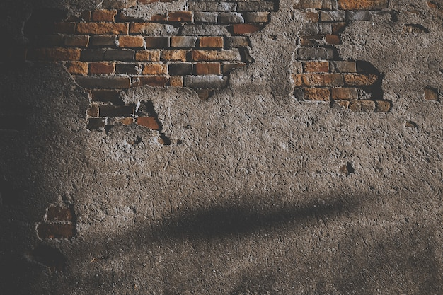 Parede de cimento danificada com tijolos