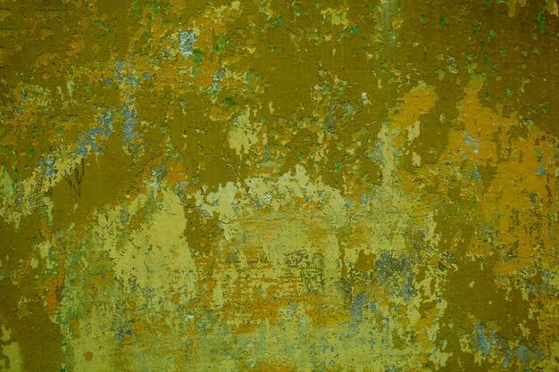 Parede de cimento sujo com rachaduras e vestígios de tinta verde sujo em uma exibição de quadro completo.