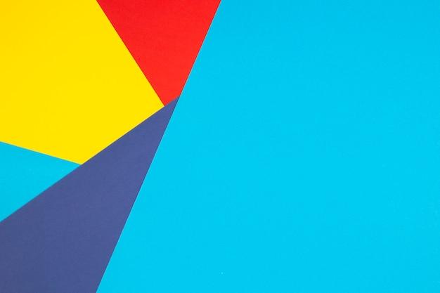 Parede de composição plana de geometria de papéis de cor com tons de amarelo, vermelho e azul